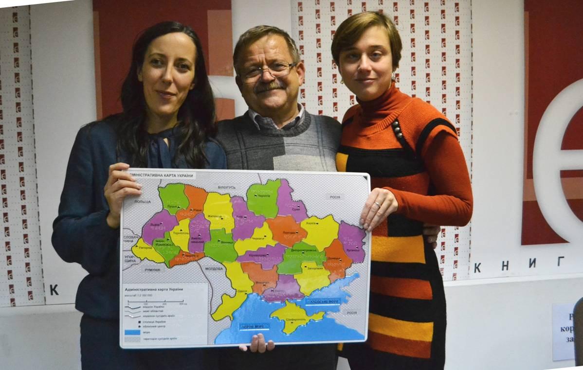 Юлія Сачук, Марек Якубовскі та Ганна Серпутько тримають разом рельєфно-графічну адміністративну карту України